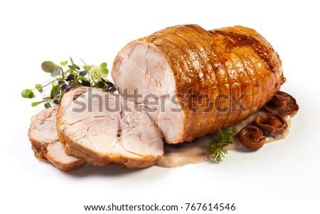 Roasted pork with sauce and garnish isolated on white.