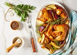 roasted potato, beetroot, green bean and chicken legs served on a white oval plate on a marble table with spices and rosemary, horizontal view from above, flat lay