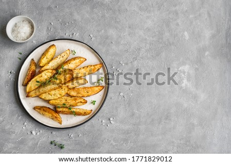 Roasted potato wedges with herbs and sea salt on plate, top view, copy space. Homemade oven baked potato snacks and sour cream sauce. Stock photo ©