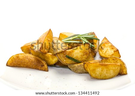 Roasted potatoes with herbs on a white plate in a restaurant