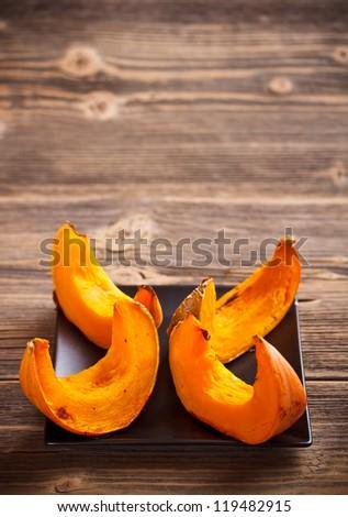 Roasted pumpkin slices served on black plate - stock photo