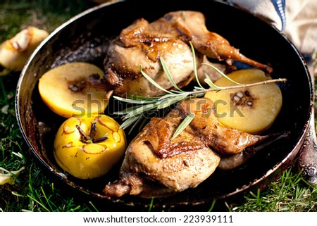 Roasted quails with quince on a cast iron skillet outdoor