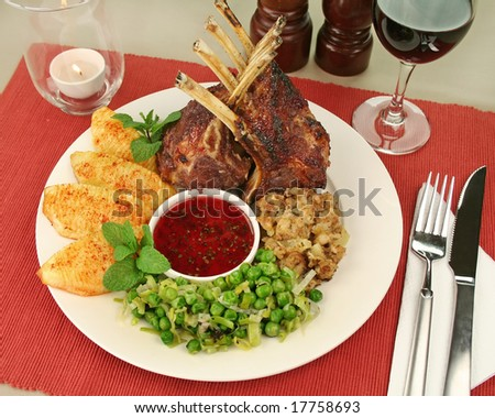 Roasted rack of lamb with red currant and mint sauce and potatoes with paprika and a pineapple stuffing with peas and leek.