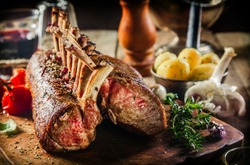 Roasted Rectangle Rack of Lamb Chops on Wooden Cutting Board Surrounded by Herbs and Fresh Ingredients