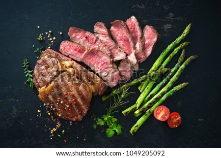 Roasted rib eye steak with green asparagus on old sheet Stock photo ©