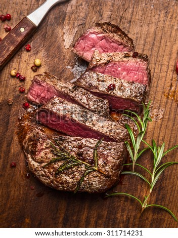 roasted  ribeye steak sliced ??on a cutting board with a fork ,rosemary and peppers, top view, close up