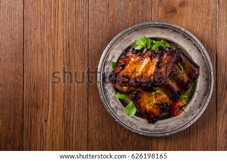 Roasted ribs, served on an old plate. Top view.