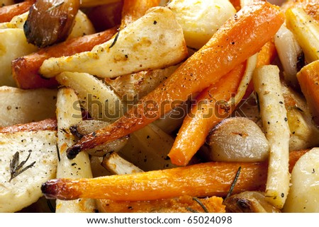 Roasted root vegetables, in close up.  Includes carrots and parsnips, plus potatoes, butternut squash, shallots and garlic bulbs.