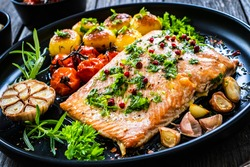 Roasted salmon steak with roast potatoes and vegetable salad served on black plate on wooden table