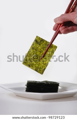 Roasted Seaweed, held with red chopsticks.  Isolated on white