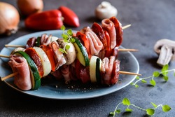 Roasted skewers with sausage, bacon, ham, zucchini, onion, pepper and mushroom