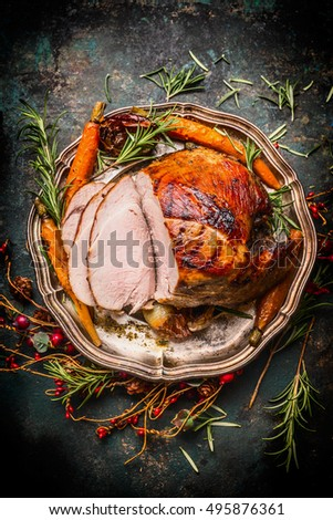 Roasted sliced pork ham and roast vegetables on dark rustic background, top view