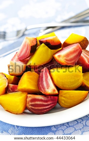 Roasted sliced red and golden beets on a plate