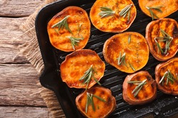 Roasted sweet potatoes with rosemary on the grill pan on the table close-up. horizontal view from above
