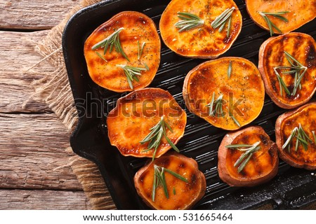 Roasted sweet potatoes with rosemary on the grill pan on the table close-up. horizontal view from above  #531665464