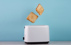 Roasted toast bread popping up of stainless steel toaster on a blue backgroun.Space for text