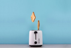 Roasted toast bread popping up of stainless steel toaster on a blue backgroun. Space for text