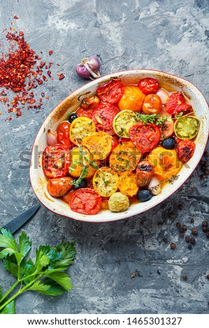 Roasted tomatoes with herbs, on baking tray.Vegetarian meal.Vegetarian food,baked tomatoes
