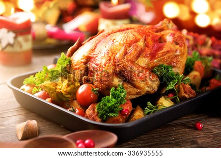 Roasted turkey garnished with Potato, Vegetables and cranberries on a rustic style table decorated with autumn leaves and candles. Christmas Dinner
