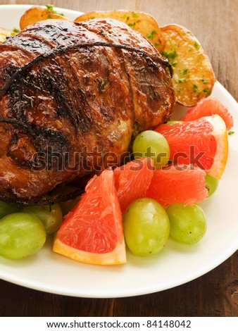 Roasted turkey roulade with potatoes and fruits. Shallow dof.