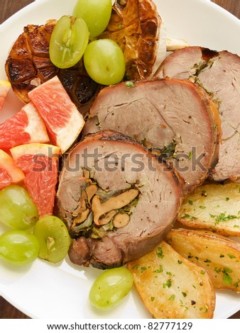 Roasted turkey roulade with potatoes, garlic and fruits. Viewed from above.