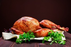 Roasted Turkey. Thanksgiving table served with turkey, decorated with greens and basil on dark wooden background. Homemade roasted chicken. Christmas holiday dinner. Space for text