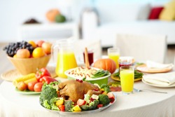 Roasted turkey with vegetables on holiday table with juice, garnish and other food served for Thanksgiving dinner