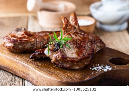 Roasted veal chops with fresh herbs on rustic wooden cutting board, pan seared steak dinner