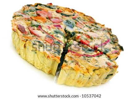 Roasted vegetable quiche, with a wedge cut out.  Delicious vegetarian food.