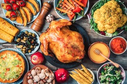 Roasted whole chicken, rice, pumpkin, corn, honey, nuts, vegetable salads over wooden background. Top view, copy space. Autumn harvest, organic vegetables. Autumn family dinner. Food concept