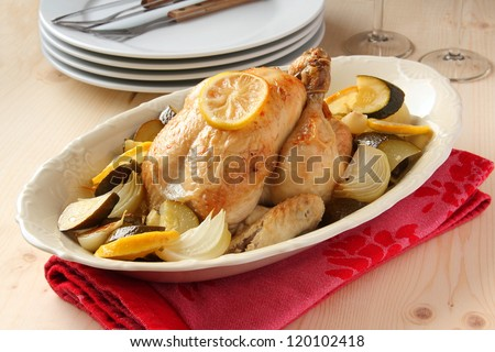 Roasted whole chicken with lemon, zucchini and onions - stock photo