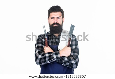 Roasting and grilling food. Man hold cooking utensils barbecue. Tools for roasting meat outdoors. Picnic and barbecue. Cooking meat in park. Masculine hobby. Bearded hipster wear apron for barbecue.