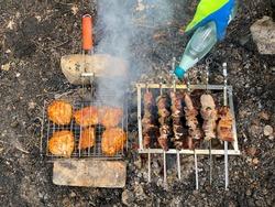 Roasts pork shish kebab and chicken shish kebab in nature. Roasting pork skewers on skewers and roasting chicken skewers on a grill on an open fire flame