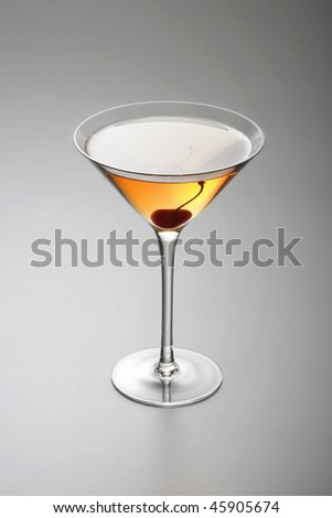 Rob Roy or Manhattan mixed drink  with cherry garnish  on grey background