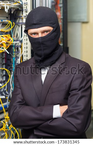 robber in black mask in the server room hack, and steals information, unauthorized downloading data