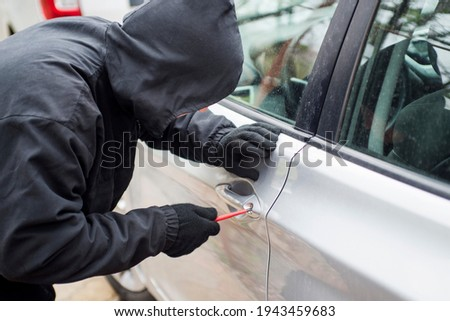 Robber man in black hoodie jacket using a screwdriver  to break lock and steal a vehicle. Car thief or theft for insurance concept. Zdjęcia stock ©