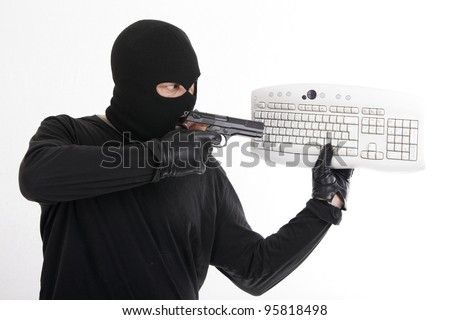 robber pointing a pistol at a computer keyboard