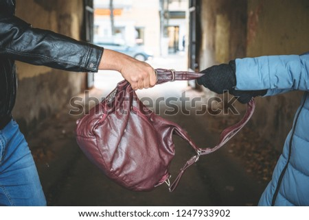Robber snatches bag from hands of woman, close up. Criminal pickpocket and crimes on city street concept Zdjęcia stock ©