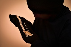 Robber with black gloves and tights over her head holding and looking at the stolen jewellery. Selective focus.