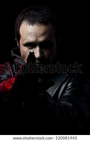 Robber with gun holding out hand against a black background