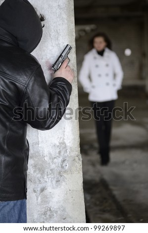 Robber with gun waiting for girl around the corner