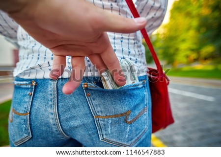 Robbery on a city street. Thief steals the tourist`s cash. Hand takes money from the back pocket of the jeans. Pickpocket rob a woman. Criminal in the city. Thieves use sneaky tricks to steal  money. Foto stock ©