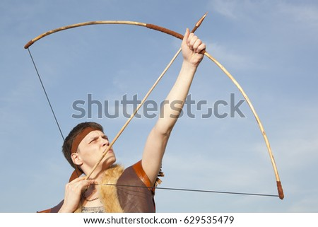 Robin Hood. Young archer in vintage clothes with arrow and long bow