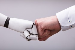 Robot And Human Hand Making Fist Bump On Grey Background