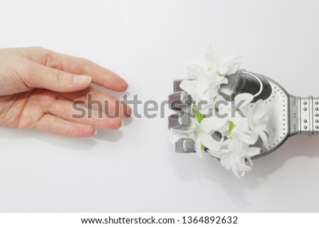 Robot and man. A robot hand gives a real person a flower. Modern technology and robotics. Robots and people nearby. Concept.