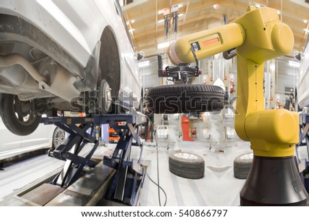 Robot arm for automotive engineering changing car wheel in modern auto repair shop