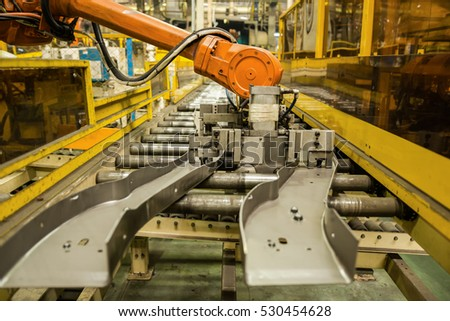 Robot arms handle tool keep automotive part to conveyor line.