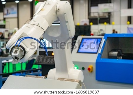 Robot hand on the background of a technical laboratory. Industrial manipulator. Setting up work for turning operations. Robotics at work. Production automation. Robots in the workplace.
