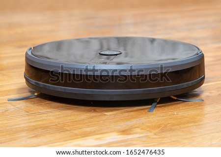 Robot vacuum cleaner on cleans wooden parquet from debris