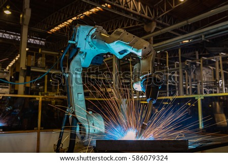 robot welding metal part in car factory